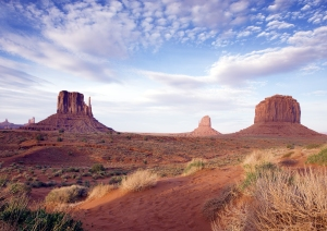 Monument Valley View. Monument Valley provides perhaps the most enduring and definitive images of the American West. The isolated red mesas and buttes surrounded by empty, sandy desert have been filmed and photographed countless times over the years for movies, adverts and holiday brochures. Because of this, the area may seem quite familiar, even on a first visit, but it is soon evident that the natural colors really are as bright and deep as those in all the pictures. The valley is not a valley in the conventional sense, but rather a wide flat, sometimes desolate landscape, interrupted by the crumbling formations rising hundreds of feet into the air, the last remnants of the sandstone layers that once covered the entire region. The area lies entirely within the Navajo Indian Reservation on the Utah/Arizona border; the state line passes through the most famous landmarks, which are concentrated around the border near the small settlement of Goulding - this was established in 1923 as a trading post, and provides basic visitor services